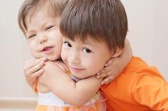 Little sister lovely hugging older brother Stock Image