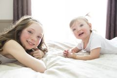 Little sister Toddler kid on bed having fun Royalty Free Stock Photos