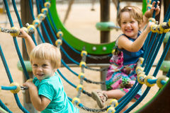 Little sisters at action-oriented playground Stock Photos