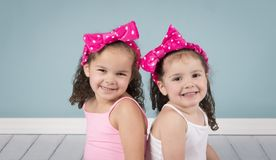 Little sisters on blue background stock photo