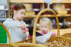 Little sisters buying hazelnuts in a food store Royalty Free Stock Images