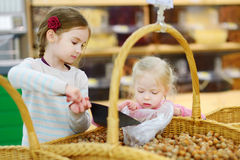 Little sisters buying hazelnuts in a food store Stock Photos