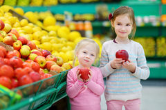Little sisters choosing apples in a food store Stock Photo