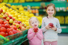 Little sisters choosing apples in a food store Royalty Free Stock Images