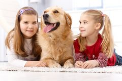 Little sisters and dog at home. Little sisters and golden retriever lying prone on floor at home, smiling stock photography