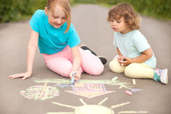 Little sisters draw with color chalk outdoors. Chalk drawings Royalty Free Stock Photos