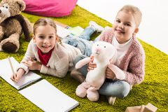 little sisters drawing and playing with toys royalty free stock image