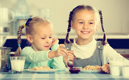 Little sisters eating porridge royalty free stock photography