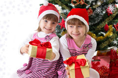 Little sisters with gifts under Christmas tree. Two little sisters with gifts under Christmas tree over white Royalty Free Stock Images