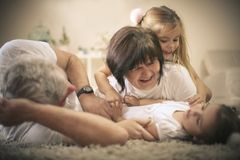 Little sisters have play with grandparents. On the move. Fun at home Royalty Free Stock Image