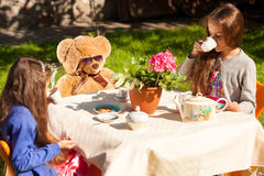 Little sisters having english breakfast with teddy bear at yard Royalty Free Stock Photo