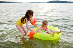 Little sisters having fun swimming in a lake using inflatable rubber Stock Image