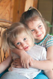 Little sisters hugging. Two little sisters sitting embracing each other at home Royalty Free Stock Image