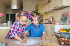Little sisters learn to prepare a dough on a kitchen Royalty Free Stock Images