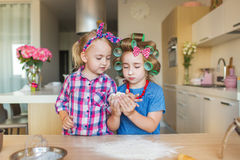 Little sisters learn to sculpt a dough on a kitchen Stock Image