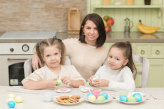 Little sisters with mom playing with Easter eggs on Easter day Stock Photos