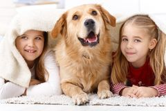 Little sisters and pet dog at home smiling. Little sisters and pet dog having fun at home, lying prone on floor, smiling under blanket Royalty Free Stock Images