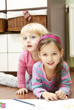Little sisters playing together in child room Stock Image