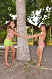 Little Sisters Playing. Two little sisters playing on the beach around a coconut tree stock photos
