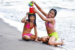 Little Sisters Playing. Two little sisters playing on the beach with beach toys stock image