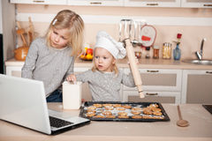 Little sisters preparing cookies and searching for Royalty Free Stock Image