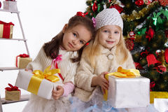 Little sisters with presents under Christmas tree. Two cute little sisters with presents under Christmas tree over white Stock Photo