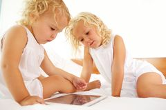 Little sisters sitting on bed and using digital tablet. Portrait of little sisters sitting on bed and using digital tablet stock photo