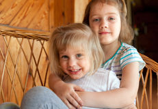 Little sisters sitting embracing each other. Two little sisters hugging at home Stock Photos