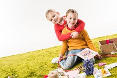 Little sisters sitting on floor while making mothers day greeting card and embracing. Isolated on white royalty free stock photography