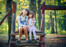 Little sisters on swing in park Royalty Free Stock Photo