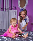 Little sisters and tablet pc Stock Images