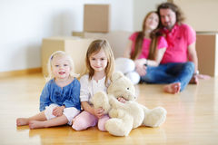 Little sisters and their parents in new home. Happy little sisters with a toy and their parents in a background in their new home Stock Photography