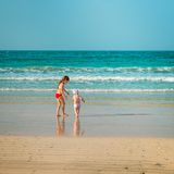 Little sisters walking along the beach Royalty Free Stock Photography