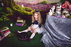 Little sitting on the floor girl as Alice in Wonderland. Little sitting on the floor girl in a beautiful dress in the image of Alice in Wonderland and magician Royalty Free Stock Photography