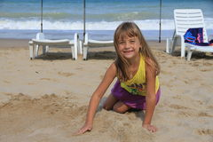 Little six-year-girl playing in the sand on the beach. Girl smiling at the camera Royalty Free Stock Photo