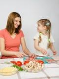 Little six year old girl joyful enthusiasm helps mum. To prepare food Stock Image