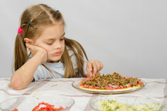 Little six year old girl sitting at table and picks unfinished pizza Royalty Free Stock Photos