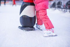 Little skater's legs standing on winter ice rink Stock Photo