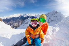 Little skier, father sit in snow on mountain peak Stock Image