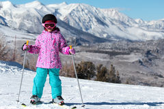 Little Skier girl on a mountain ski. Picture of little skier girl with a mountain ski, ski boots, helmet and goggles against the backdrop of snow-capped stock photo