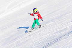 Little skier racing in snowy mountain slope Stock Photos