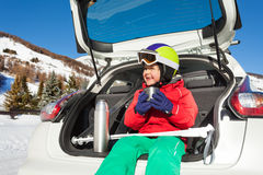 Little skier sitting in car boot and drinking tea. Happy little boy skier in safety helmet and goggles sitting in the car boot, drinking warm tea stock image