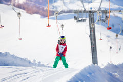 Little skier using a button lift on the slope Stock Photography