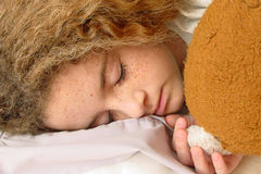 Little Sleeping Beauty. A closeup photo of a little girl asleep with her teddy bear stock images