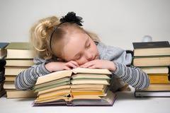 Little sleeping  among  books Stock Photos
