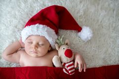 Little sleeping newborn baby boy, wearing Santa hat stock photo