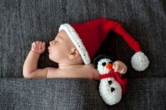 Little sleeping newborn baby boy, wearing Santa hat and holding royalty free stock photos