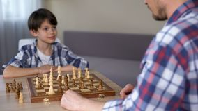 Little smart boy winning chess, handshaking with his proud father, hobby. Stock footage stock video