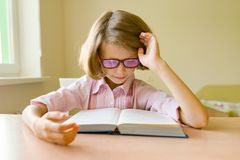 Little smart girl with glasses reading a large book sitting at her desk. School, education, knowledge and children.  royalty free stock image