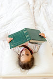 Little smart girl reading big old book in bed Royalty Free Stock Photos